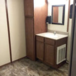 Photo of the inside of Moen's 8 stall VIP Restroom Trailer showing sink, mirror, and storage cabinet.