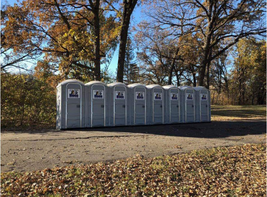 8 portable toilets lined up neatly on a path during the fall.