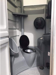 The inside of a VIP flushing portable toilet unit. It features one flushing toilet with a black lid, sink, urinal, paper towel roll and paper towel dispenser.
